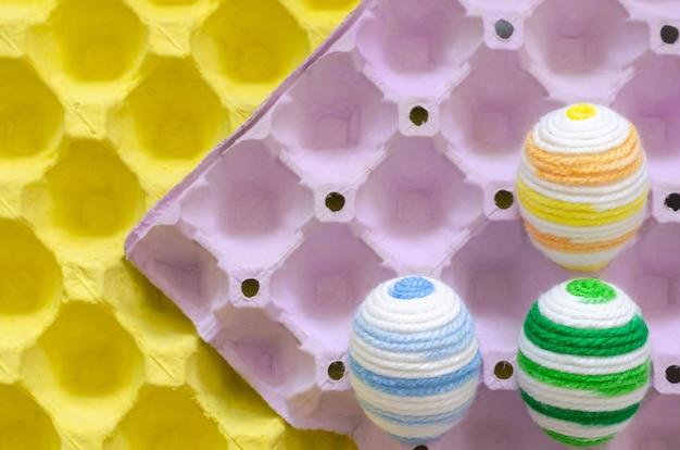 Des oeufs colorés pour le jour de pâques et le festival sont placés dans un plateau à oeufs violet et jaune.