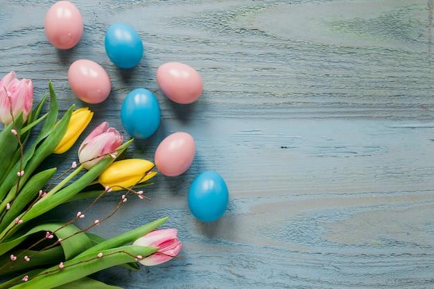 Oeufs colorés près de tulipes et saule