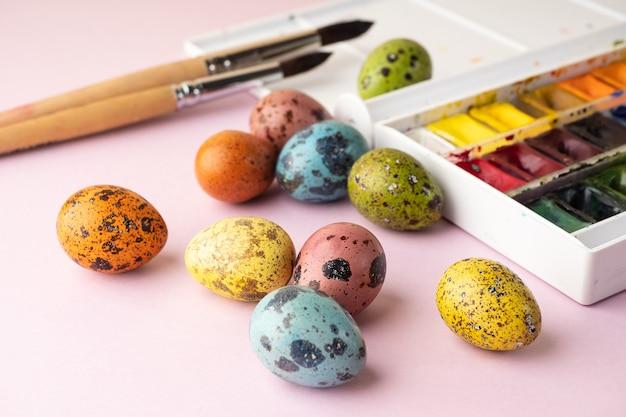 Oeufs à colorier pour pâques. peinture, pinceaux, œufs de caille sur fond rose. préparation pour la célébration de pâques, décorations pour les vacances, arrière-plan. concept créatif.
