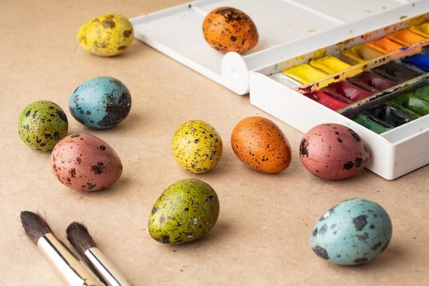 Oeufs à colorier pour pâques. peintures, pinceaux, œufs de caille sur fond artisanal. préparation pour la célébration de pâques, décorations pour les vacances, arrière-plan. concept créatif.