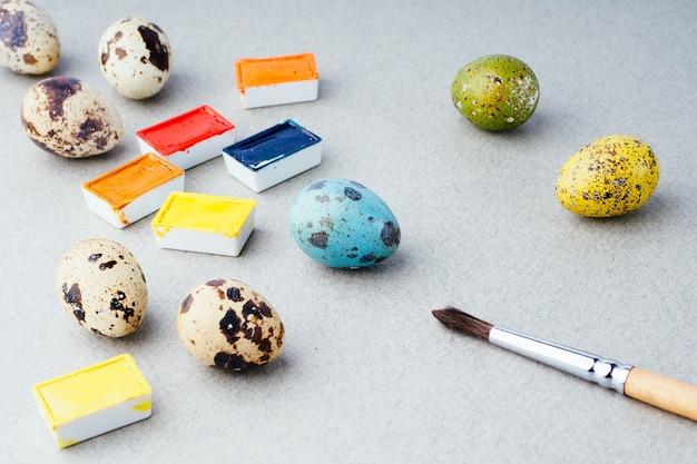 Oeufs à colorier pour pâques. peintures, pinceaux, œufs de caille sur fond gris. préparation pour la célébration de pâques, décorations traditionnelles, arrière-plan. concept créatif.