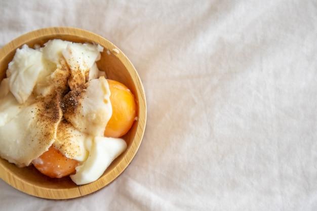 Œufs à la coque avec du poivre et du sel dans une tasse en bois.