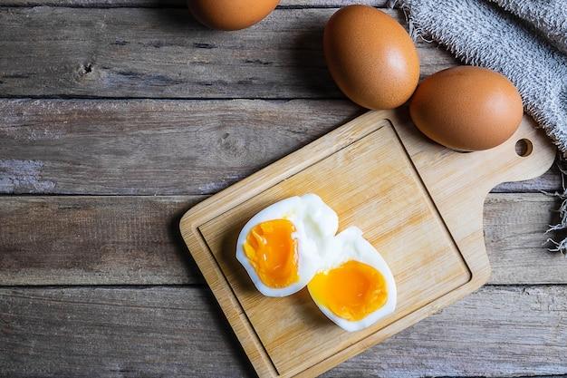 Œufs à la coque et œufs crus sur une table en bois