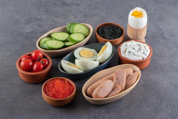 Œufs à la coque avec des saucisses et des concombres tranchés placés sur une table en pierre.