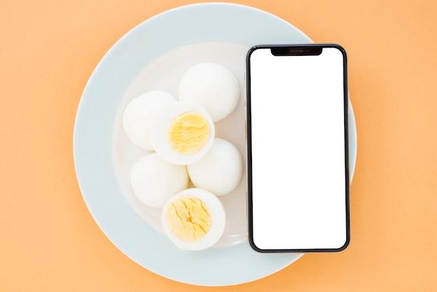 Œufs à la coque et téléphone portable avec écran blanc, affichage d'un smartphone sur une plaque blanche en céramique