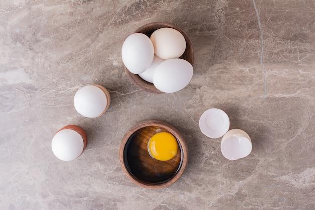 Œufs, coquilles d'œufs et jaune d'œuf dans une tasse en bois