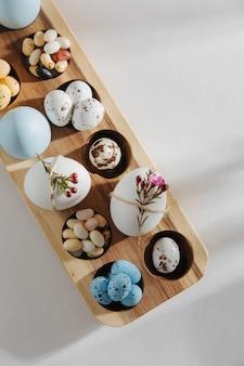 Oeufs de couleur naturelle avec des fleurs, des oeufs de pâques en chocolat, des bonbons et des bonbons à la gelée dans une boîte à oeufs en bois avec des lumières du soleil. compositions élégantes. mise à plat, vue de dessus