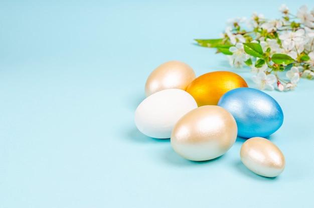Oeufs de couleur perle pour pâques avec des branches de cerisier en fleurs sur bleu