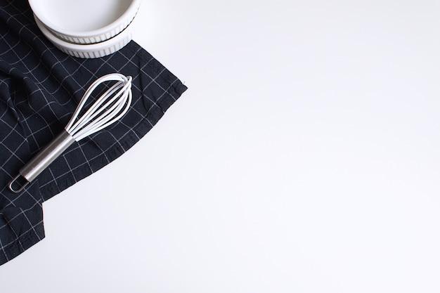 Oeufs crus fouetter le moule et la serviette noire à carreaux