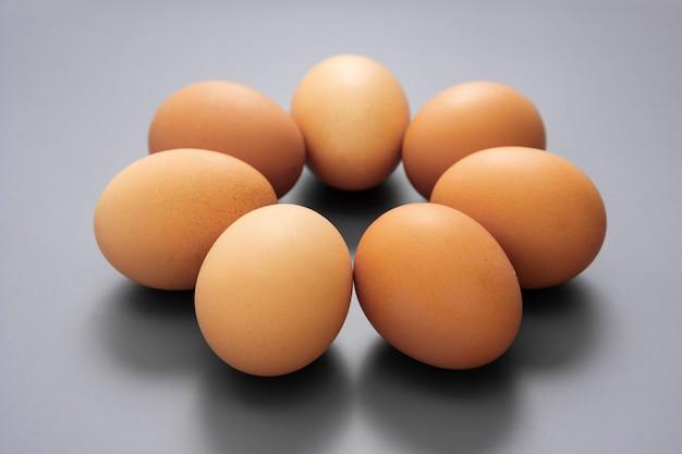 Oeufs crus isolés sur table grise, aliments protéinés.