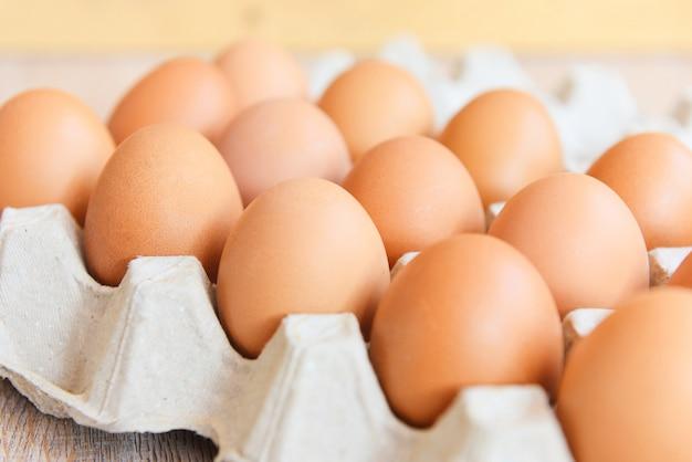 Oeufs dans une boîte à œufs sur fond de bois / close up of raw chicken eggs bio food