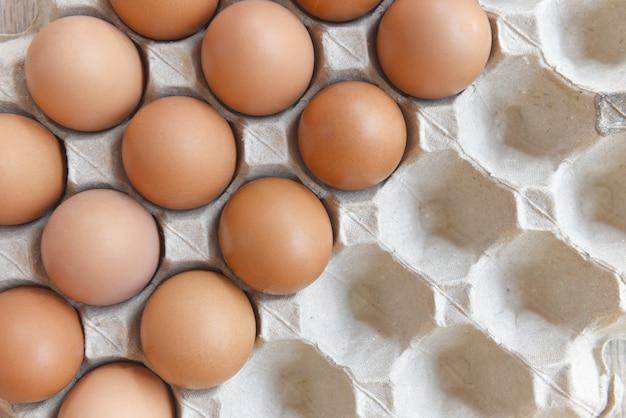 Oeufs dans une boîte à œufs sur fond en bois vue de dessus / close up of raw chicken eggs bio food