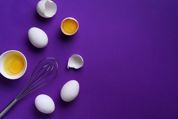 Oeufs dans un bol blanc avec un fouet sur fond violet