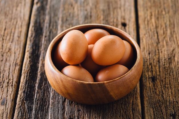 Oeufs dans un bol en bois sur table en bois