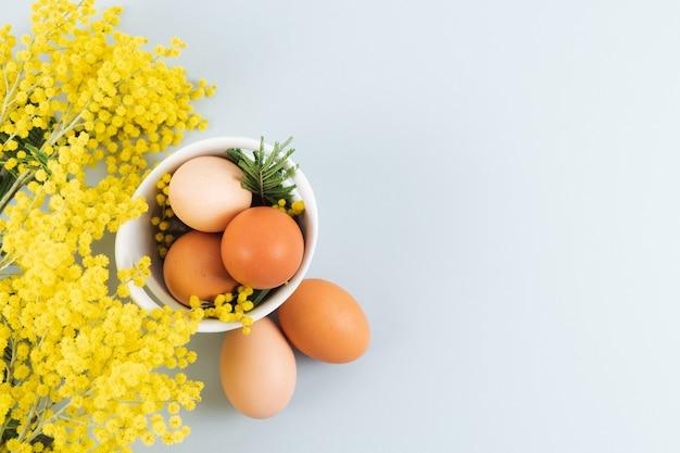 Oeufs dans un bol de différentes nuances en ligne sur fond bleu avec des fleurs jaunes. copiez l'espace. vue de dessus.