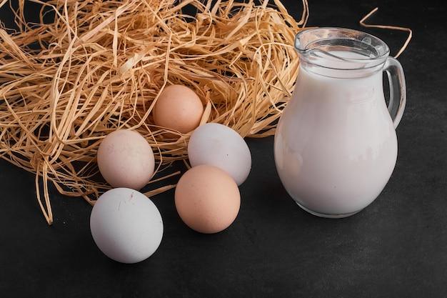 Oeufs dans le nid sur une surface noire avec un pot de lait de côté.