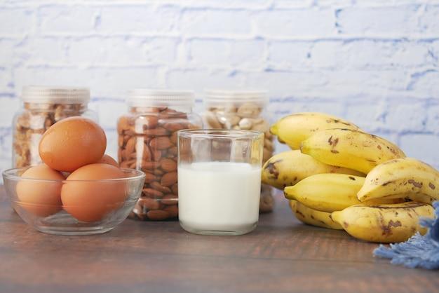 Oeufs dans un récipient en plastique lait et noix d'amande dans la table
