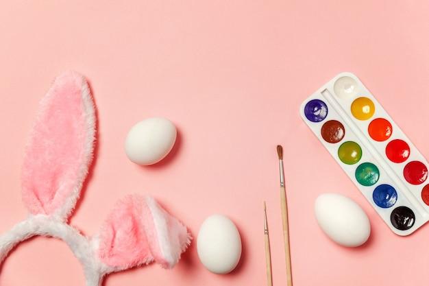 Oeufs décoratifs peintures colorées et costume de fourrure oreilles de lapin isolé sur table rose