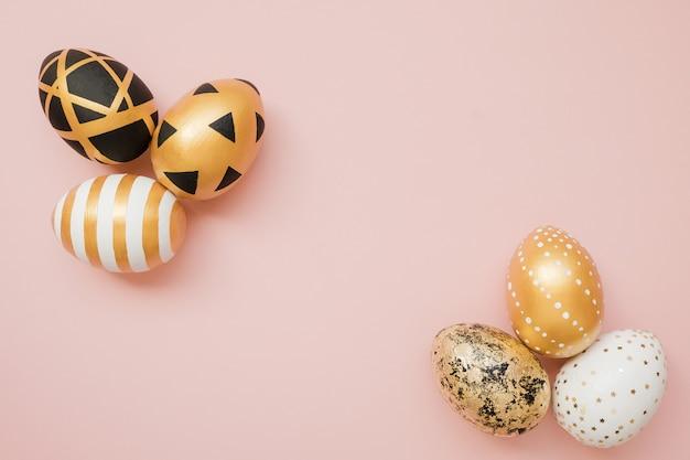Oeufs décorés de pâques doré sur fond rose pastel