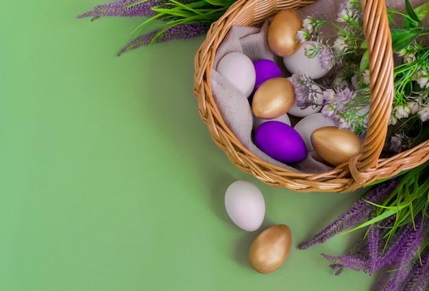 Oeufs dorés, blancs, violets dans un panier