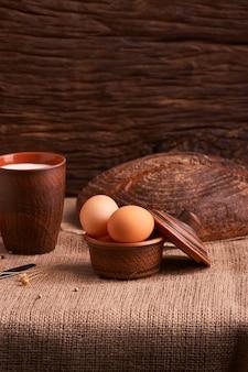 Oeufs avec du pain et des ustensiles de cuisine sur vintage en bois. nourriture savoureuse