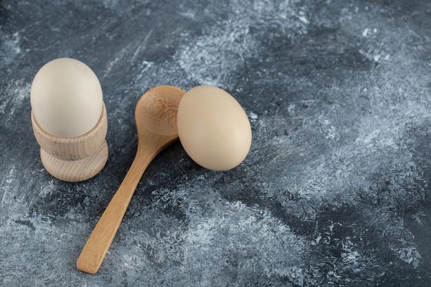 Œufs durs et cuillère en bois sur marbre.