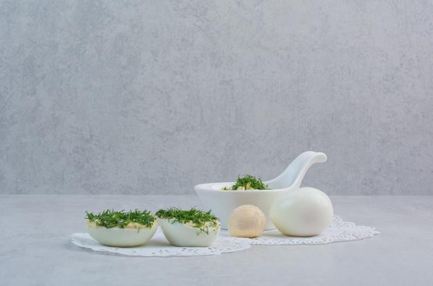 Oeufs durs avec des verts sur fond blanc.