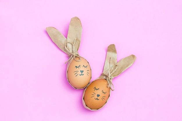 Œufs d'ester peints comme un lapin sur un bureau rose