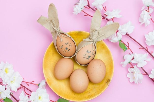 Oeufs d'ester peints comme un lapin dans une tasse en bois sur un bureau rose