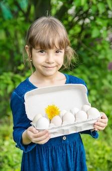 Des oeufs faits maison dans les mains d'un enfant.