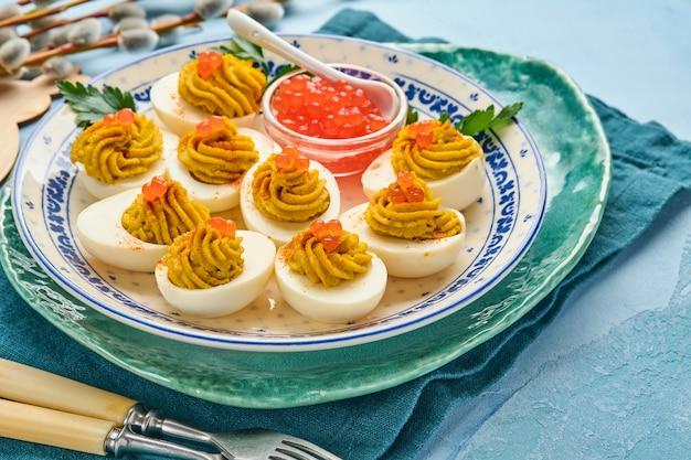 Oeufs farcis au caviar rouge et paprika sur assiette pour apéritif table de pâques, vue de dessus, espace de copie. plat traditionnel pour joyeuses fêtes de pâques.