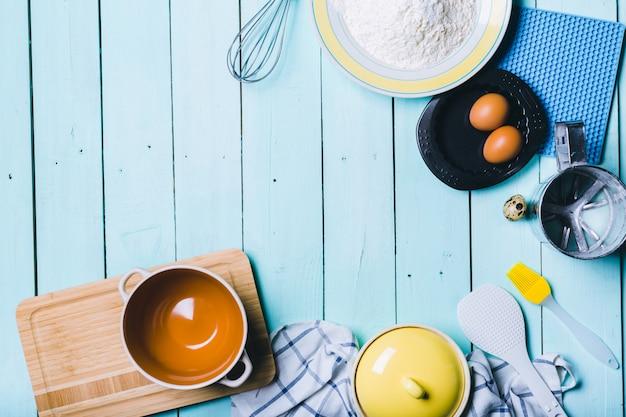 Oeufs et farine avec un rouleau à pâtisserie sur fond en bois