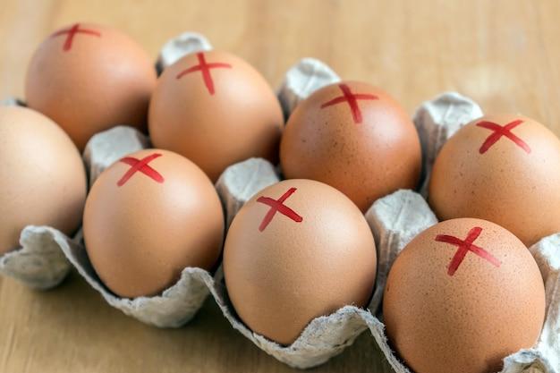 Œufs de ferme brune avec une croix rouge dans un carton blanc. rappel d'oeufs