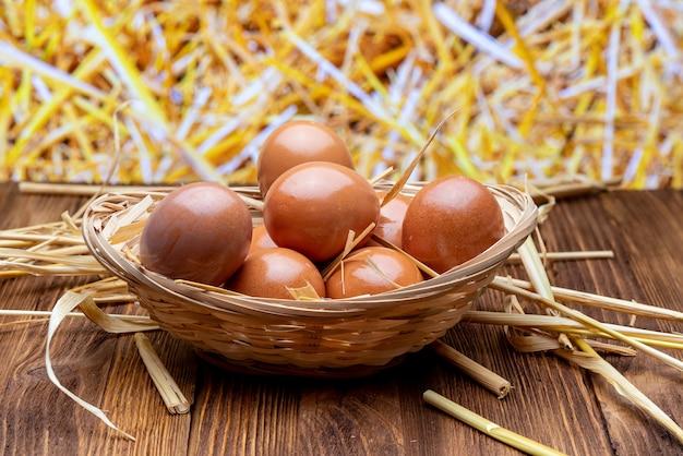 Œufs frais et crus dans un panier en osier et de la paille. image rustique et granaja.
