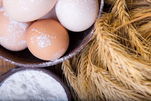 Œufs frais dans un bol brun, blé et farine sur une surface en bois