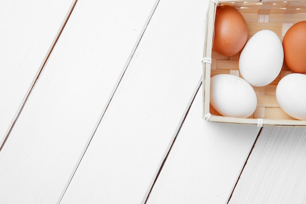 Œufs frais dans un panier sur un fond en bois.
