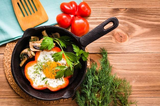 Œufs frits au poivre, herbes et champignons dans la poêle en fer