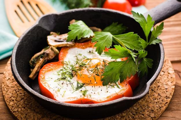 Œufs frits au poivre, persil et champignons dans la poêle en fer