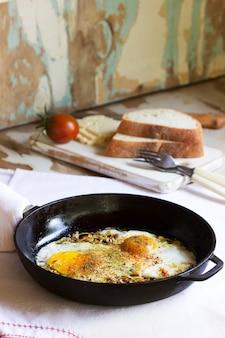 Œufs frits aux oignons et épices dans une poêle en fonte. mise au point sélective.