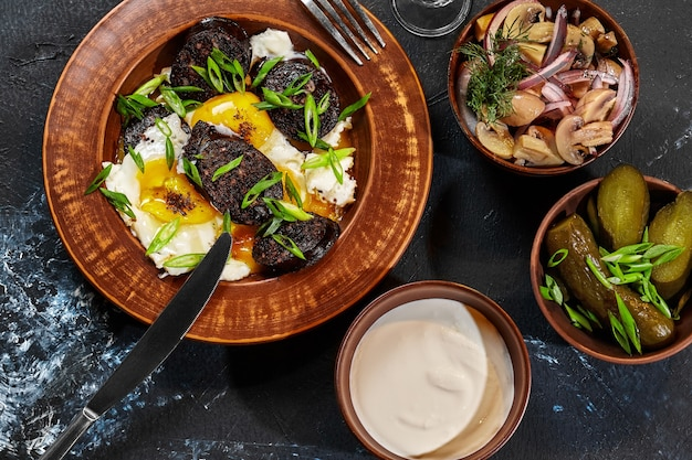 Oeufs frits avec boudins, cornichons à la crème sure et champignons marinés