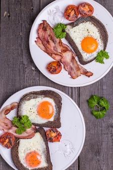 Oeufs frits dans du pain de seigle avec du bacon, des tomates et du persil dans un style rustique.
