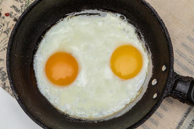 Oeufs frits dans une poêle en fer rustique pour le petit-déjeuner. vue de dessus.