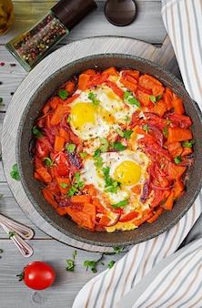 Oeufs frits avec des morceaux de citrouille, oignons rouges et tomates. petit déjeuner savoureux. vue d'en-haut