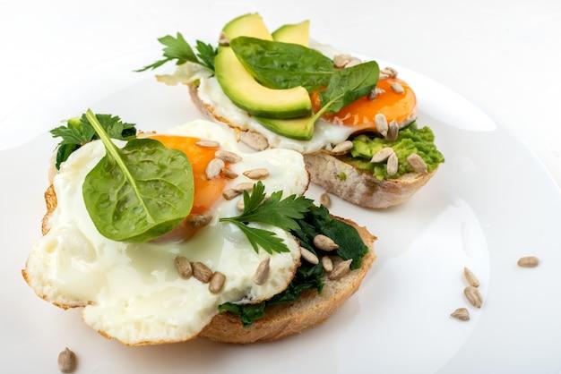 Oeufs frits sur un pain grillé avec avocat, épinards et graines sur une plaque blanche.