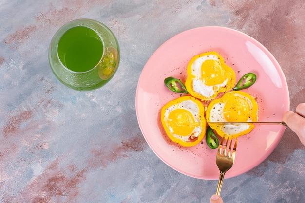 Œufs frits en tranches de poivrons jaunes et une tasse en verre de jus vert.