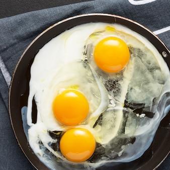 Oeufs frits de trois œufs dans une casserole