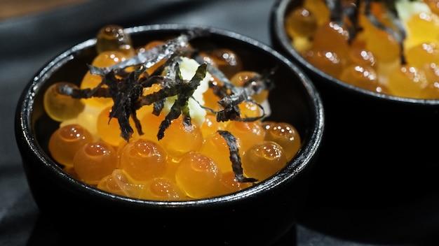 Oeufs d'ikura saumon oeufs d'ikura servis avec du riz et garnir d'algues japonaises ikura don très célèbre