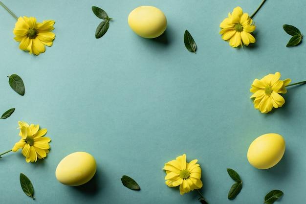 Oeufs jaunes et fleurs sur fond de papier vert. carte minimale de pâques. mise à plat, espace copie.