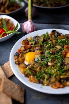 Oeufs légumes cuits salés poivrés avec miches de pain à l'intérieur de la plaque blanche