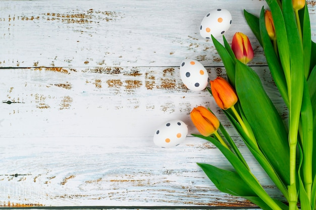 Oeufs mouchetés peints de pâques multicolores dans le panier sur table en bois blanc avec des tulipes